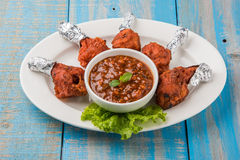 Chicken lollipop or chicken winglet. Served with tomato chutney, a chinese preparation Stock Image