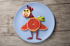 Chicken made of fruits. On plate and wooden desk royalty free stock image