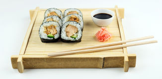 Chicken maki rolls with pickled ginger and soy sauce on a rustic bamboo mat and tray Stock Image