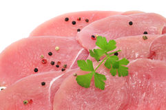 Chicken meat. Some slices of raw chicken meat with peppercorns and parsley on white background stock images