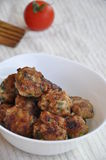 Chicken meat balls. Meat balls in a bowl with a wooden spoon and a tomatoe on the bckground Royalty Free Stock Photography
