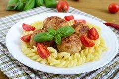 Chicken meat balls, pasta fusilli, tomatoes, basil Royalty Free Stock Photos