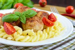 Chicken meat balls, pasta fusilli, tomatoes, basil on a white plate Royalty Free Stock Image