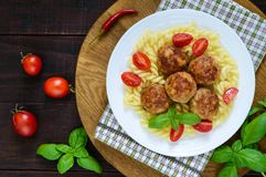 Chicken meat balls, pasta fusilli, tomatoes, basil on a white plate on a wooden tray. Stock Photos