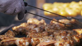 Chicken meat cooking on a barbecue grill. Grilled chicken on the grill. Chicken cooking on a barbeque grill. Close up. Hand using tongs for turning meat on the stock footage