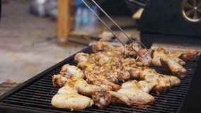 Chicken meat cooking on a barbecue grill. Grilled chicken on the grill. Chicken cooking on a barbeque grill. Hand using tongs for turning meat on the grill stock video footage