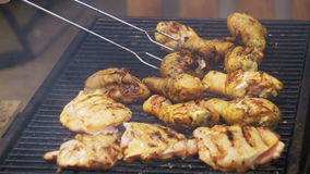 Chicken meat cooking on a barbecue grill. Grilled chicken on the grill. Chicken cooking on a barbeque grill. Hand using tongs for turning meat on the grill stock video