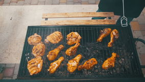 Chicken meat cooking on a barbecue grill in slow motion. Grilled chicken on the grill. Chicken cooking on a barbeque grill. Slow motion in 96 fps. Hand using stock video