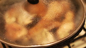 Chicken meat is fried under a transparent lid. Home Preparing Of Chicken.Chicken is fried in a lot of sunflower oil with a toasted crust,Chicken meat is fried stock footage
