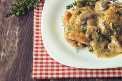 Chicken meat with mushroom sauce and thyme. On rustic wooden background Royalty Free Stock Images