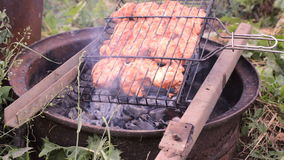 Chicken meat pieces being fried on a charcoal grill stock video footage