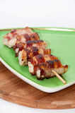 Chicken meat rolled in bacon on a green plate Stock Image