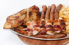 Chicken meat rolled in bacon and homemade sausages served on whi Royalty Free Stock Photos