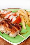 Chicken meat rolled in bacon with tomato and onion salad Royalty Free Stock Image