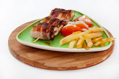Chicken meat rolled in bacon with tomato and onion salad Royalty Free Stock Photos