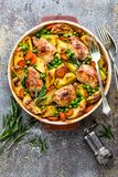 Chicken meat, thighs baked with potato, carrot and green peas. Top view Royalty Free Stock Photo
