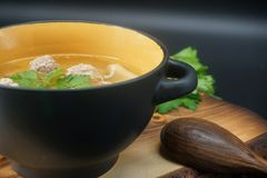 Chicken meatball soup on the cutting board. Chicken meatball soup and ingredients on wooden table. Close-up. The dish is on the cutting board stock images