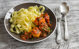 Chicken meatballs in tomato sauce and fettuccine pasta in a brown bowl Stock Images