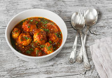 Chicken meatballs with tomato sauce in a white bowl on bright wooden surface Royalty Free Stock Photos