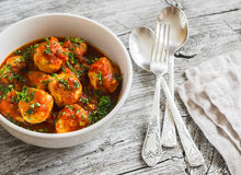 Chicken meatballs with tomato sauce in a white bowl on bright wooden surface. Stock Image