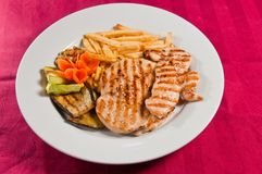 Chicken medallions. Whit french fries and grilled vegetables Stock Photos