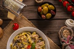Chicken and mushroom pasta rustic top view. Chicken and mushroom tagliatelle shot on wood boards top view close-up with a copper pot loose mushrooms vine tomato Royalty Free Stock Photography