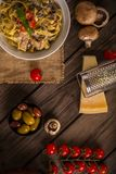 Chicken and mushroom pasta rustic top view. Chicken and mushroom tagliatelle shot on wood boards top view close-up with a copper pot loose mushrooms vine tomato Royalty Free Stock Photos
