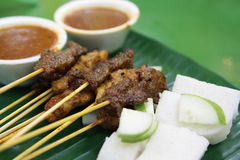 Chicken and Mutton Satay. A dish of marinated meat in sticks, grilled and served with cucumbers, onions, steamed rice and spicy peanut dip sauce Royalty Free Stock Image