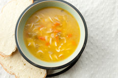 Chicken noodle soup. A steaming bowl of chicken noodle soup with fresh slices of sourdough bread thickly buttered on the side. the ultimate comfort food and cold Stock Photos