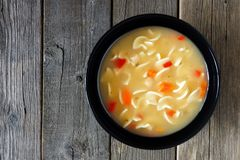 Chicken noodle soup, above view on rustic wood Stock Photo