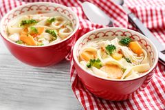 Chicken noodle soup in bowls. On wooden table royalty free stock photo