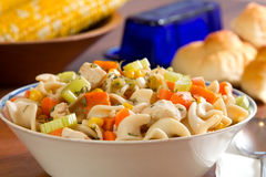 Chicken Noodle Soup. With corn, butter and bread in the background Stock Photo