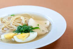 Chicken noodle soup with egg and greenery Stock Image