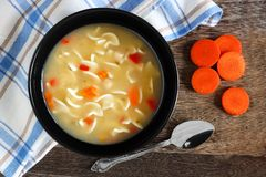 Chicken noodle soup, overhead scene on rustic wood Stock Image