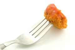 Chicken Nugget on Fork. A photo of a chicken nugget on a fork over a white background Royalty Free Stock Photography