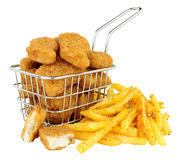 Chicken Nuggets And French Fries In A Small Wire Frying Basket. Breadcrumb covered chicken nuggets and French fries in a small wire frying basket isolated on a stock photos