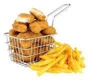 Chicken Nuggets And French Fries In A Small Wire Frying Basket. Breadcrumb covered chicken nuggets and French fries in a small wire frying basket isolated on a royalty free stock photo