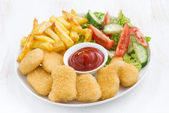 Chicken nuggets, french fries and vegetable salad Royalty Free Stock Photography