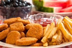 Chicken Nuggets and French Fries. With watermelon and blueberries in the background Royalty Free Stock Photos