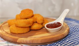 Chicken nuggets. Fried chicken nuggets on a wooden board with red sauce Royalty Free Stock Images