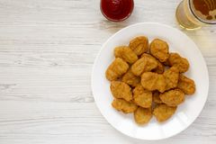 Chicken nuggets, ketchup and glass of cold beer on a white wooden background. Overhead, from above, flat lay. Copy space.  stock photos