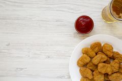 Chicken nuggets, ketchup and glass of cold beer on a white wooden background. Overhead, from above, flat lay. Copy space.  stock image