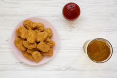 Chicken nuggets with ketchup and glass of cold beer on a white wooden background, top view. Overhead, from above, flat lay.  stock photo