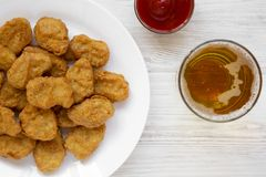 Chicken nuggets, ketchup and glass of cold beer on a white wooden surface. Overhead, from above, flat lay.  stock image