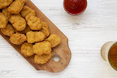 Chicken nuggets with ketchup and glass of cold beer on a white wooden table, overhead view. Flat lay, from above, top view. Close-. Up stock image