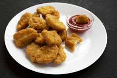 Chicken nuggets with ketchup on a white plate on a black background, side view. Close-up.  royalty free stock image