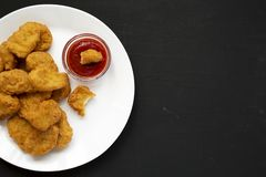 Chicken nuggets with ketchup on a white plate on a black background, top view. Flat lay, overhead, from above. Copy space.  royalty free stock photo