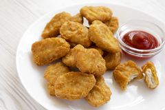 Chicken nuggets with ketchup on a white plate on a white wooden background, low angle view. Close-up.  royalty free stock photos