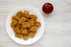 Chicken nuggets and ketchup on a white wooden background. Overhead, from above, flat lay.  royalty free stock images