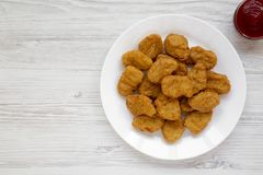 Chicken nuggets and ketchup on a white wooden background. Overhead, from above, flat lay. Copy space.  royalty free stock photography